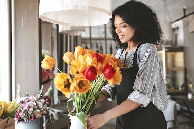 カラフルなチューリップの花束を作成するエプロンの美しい花屋。花を扱う暗い巻き毛のかわいいアフリカ系アメリカ人の女の子