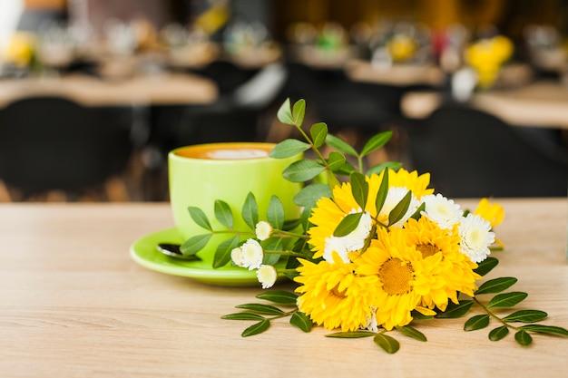デフォーカスコーヒーショップの背景を持つ木製の机の上の美しい花とコーヒーカップ