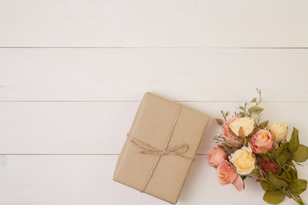 Красивый цветок и подарочная коробка на деревянном фоне с романтическим