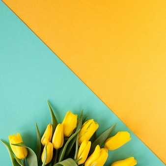 Beautiful flower arrangement. yellow flowers tulips, empty frame for text on a yellow background. wedding. birthday valentine's day. mothers day. flat lay, top view, copy space