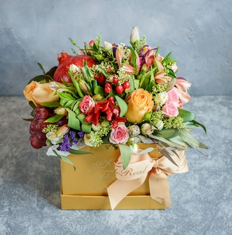 A beautiful flower bouquet with pomegranate and grapes in yellow box with bowtie