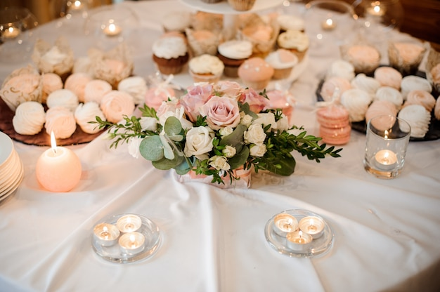 Beautiful flower composition and candles decorating a festive table served with cakes