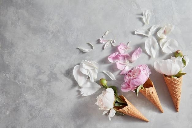 Красивый цветок в вафельном рожке на сером фоне бетона