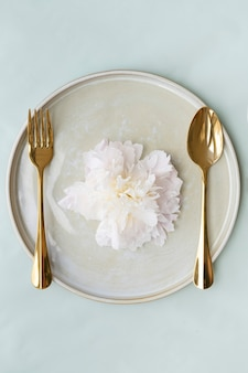 황금 숟가락과 포크가 있는 접시에 있는 아름다운 꽃