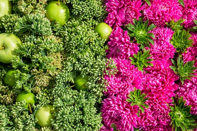 Beautiful flowers background with apple in top view