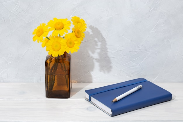 Beautiful flowers in bottle and blue diary on wooden table background. writing or drawing concept. copy space