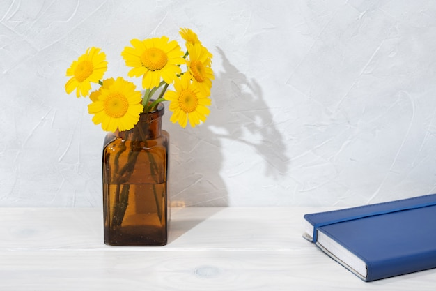 Beautiful flowers in bottle and blue diary on wooden table. writing or drawing concept. copy space