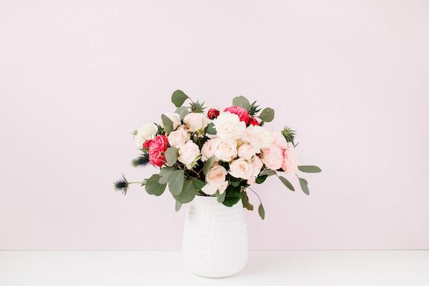 Красивый букет цветов: напыщенные розы, голубой эрингиум, ветки эвкалипта в вазоне у бледно-пастельно-розовой стены.