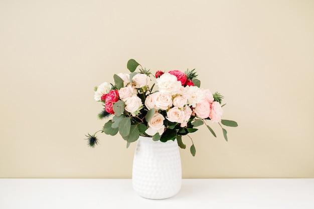 Красивый букет цветов в кашпо перед бледно-пастельно-бежевой стеной