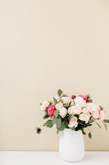 淡いパステル ベージュの壁の前に植木鉢に美しい花の花束