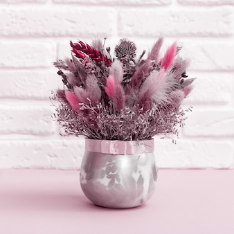 Beautiful flowers bouquet pink and red colored with dried plants, flower, grass. handmade floral decoration against white brick wall.