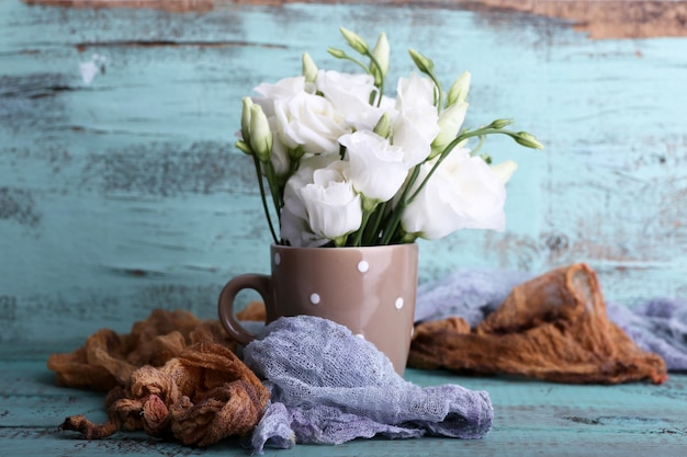 Beautiful flowers in cup on wooden surface