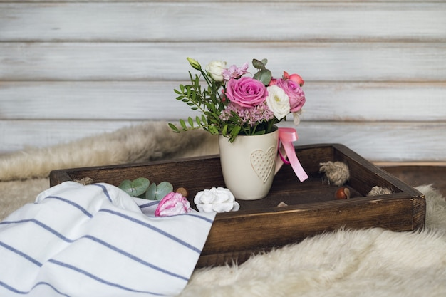 Beautiful flowers in cup on wooden