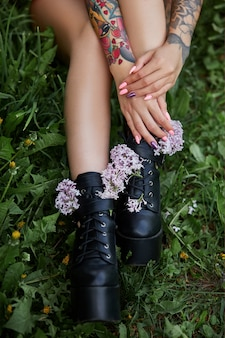 Beautiful flowers in hands of a girl with tattoos