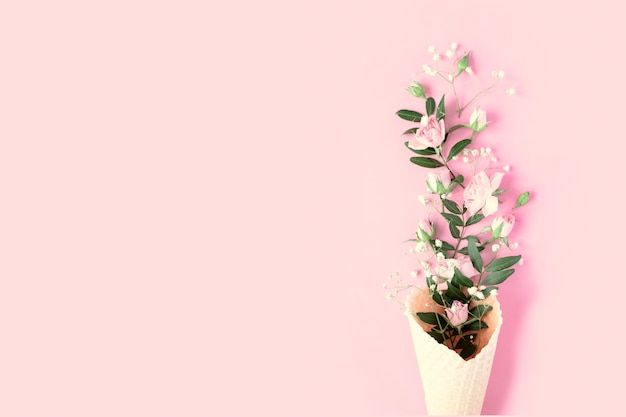 Beautiful flowers in ice cream cone on pink background. flat lay