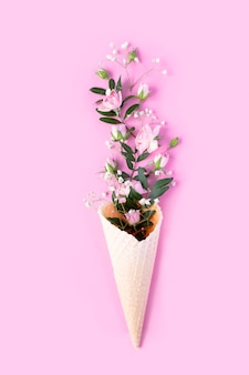 Красивые цветы в рожке мороженого на розовом фоне. плоская планировка