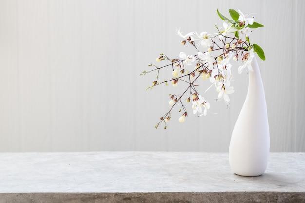 コピースペース、柔らかなトーンの静物と白い木の背景を持つコンクリートのテーブルに設定されたモダンな花瓶の美しい花