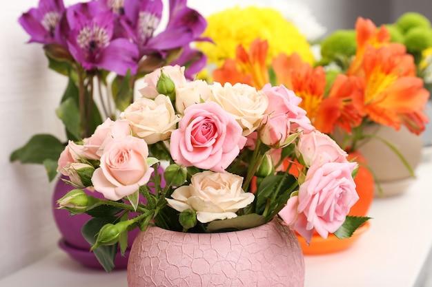 Красивые цветы в горшках на светлой поверхности