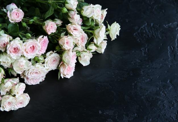 黒の背景に美しい花。バラの花束。完璧なフラットレイ。幸せな母の休日のはがき。国際女性の日の挨拶。広告やプロモーションのためのスタイリッシュなアイデア。