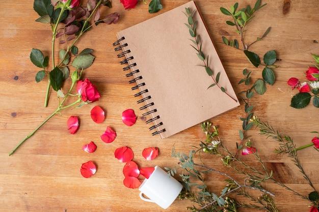 Красивые цветы на деревянном столе с тетрадью. работа флориста. доставка цветов.