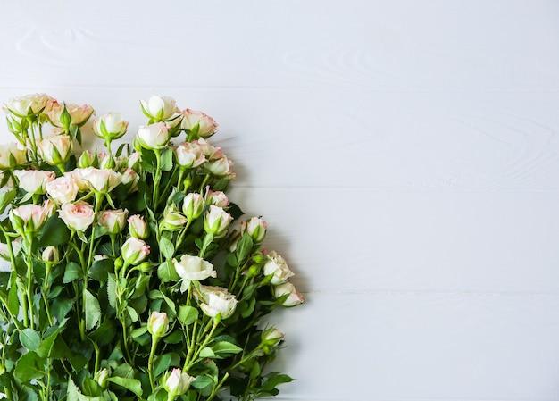 白い背景の上の美しい花。バラの花束。完璧なフラットレイ。幸せな母の休日のはがき。国際女性の日の挨拶。広告やプロモーションのための誕生日のアイデア。