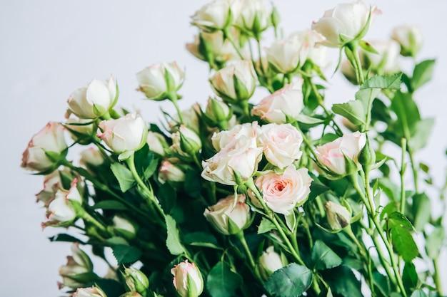 白い背景の上の美しい花。バラの花束。完璧なフラットレイ。幸せな母の休日のはがき。国際女性の日の挨拶。広告やプロモーションのためのスタイリッシュなアイデア。