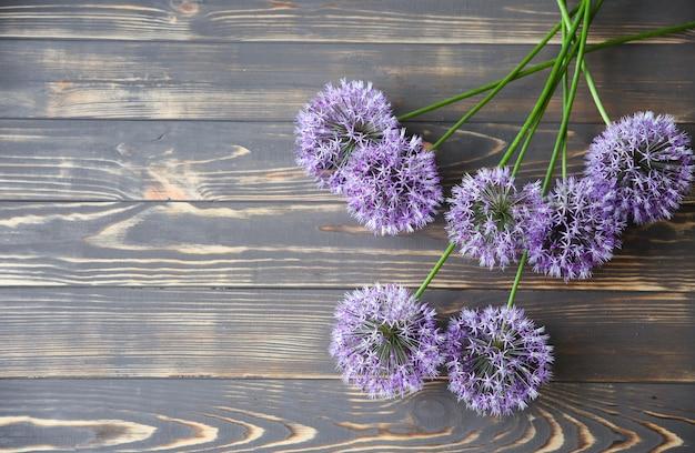 나무 배경에 아름 다운 꽃입니다. 부추 꽃다발. 꽃잎이 있는 완벽한 플랫 레이. 해피 어머니의 휴일 엽서입니다. 국제 여성의 날 인사말. 광고 또는 판촉을 위한 세련된 아이디어.