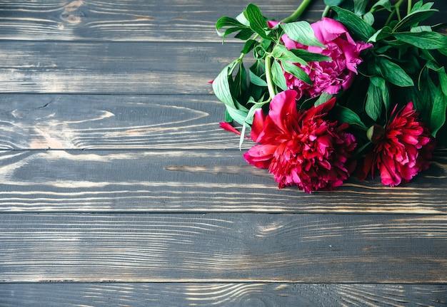 木製の背景に美しい花。牡丹の花束。花びらが付いた完璧なフラットレイ。幸せな母の休日のはがき。国際女性の日の挨拶。広告やプロモーションのためのスタイリッシュなアイデア。
