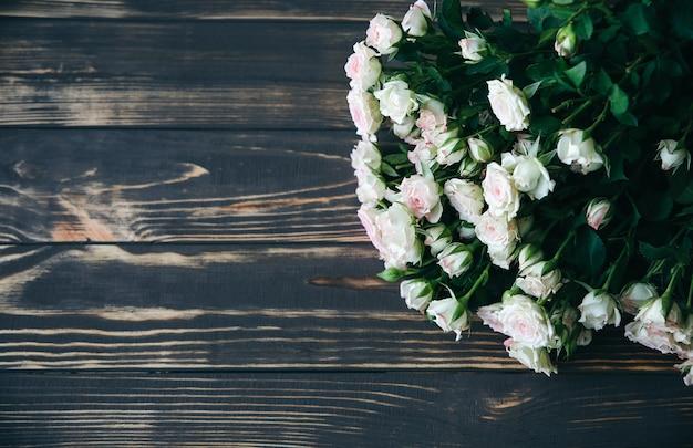 木製の背景に美しい花。バラの花束。花びらが付いた完璧なフラットレイ。幸せな母の休日のはがき。国際女性の日の挨拶。広告やプロモーションのためのスタイリッシュなアイデア。