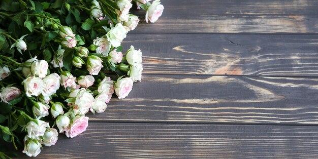 나무 배경에 아름 다운 꽃입니다. 장미 꽃다발. 꽃잎이 있는 완벽한 플랫 레이. 해피 어머니의 휴일 엽서입니다. 국제 여성의 날 인사말. 광고 또는 판촉을 위한 세련된 아이디어.