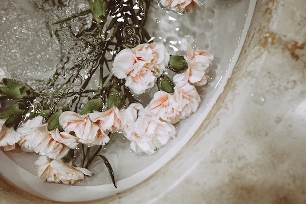 Beautiful flowers in a sink with water. aesthetic beauty