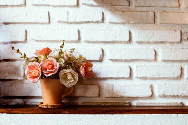Beautiful flowers in vase on brick wall background in vintage color tone