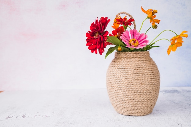 Beautiful flowers in the vase on grunge backdrop