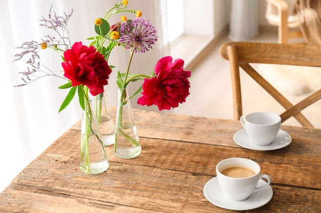 Beautiful flowers in vases as floral decor on wooden table