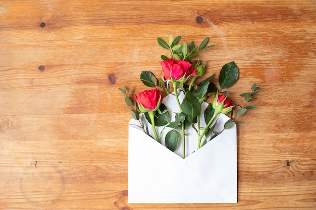Beautiful flowers on a wooden table with an envelope. the work of the florist. flower delivery.