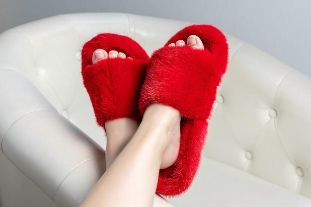 Красивые пушистые меховые тапочки на женских ножках.