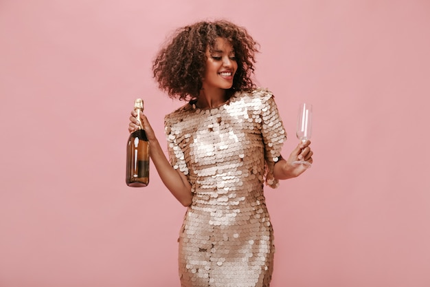 Beautiful fluffy haired girl in fashionable shiny dress smiling with closed eyes and holding glass and bottle with wine on isolated wall..