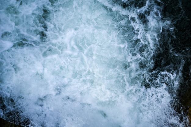 Красивое пенистое море. вода течет из открытых шлюзовых ворот плотины. голубая морская вода с брызгами. текстура волн