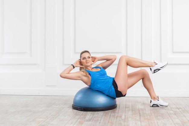Красивая сосредоточенная спортивная молодая спортивная блондинка в черных шортах и синем топе работает в тренажерном зале, делая упражнения для мышц живота на тренажере баланса босу, ложится на фитнес-босу, в помещении