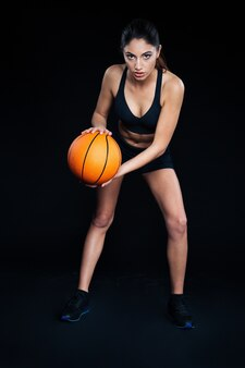 Beautiful focused young sportswoman with orange ball ready to play basketball over black background