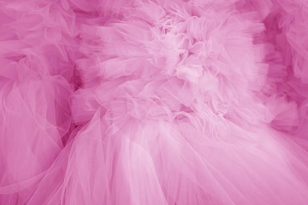 Красивые складки прозрачной ткани розового цвета. текстильная текстура.