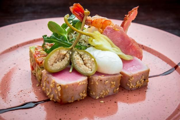 Красивая еда: стейк из тунца в кунжуте, лайме и свежий салат крупным планом на тарелке на столе.