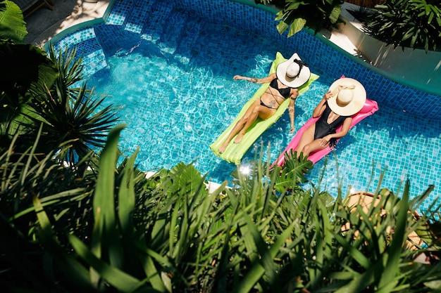 태양으로부터 얼굴을 덮는 밀짚 모자와 함께 네온 녹색과 분홍색 떠 있는 매트리스에서 휴식을 취하는 젊은 여성에게 아름다운