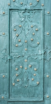 Beautiful forged patterns on an emerald-colored door background. close-up