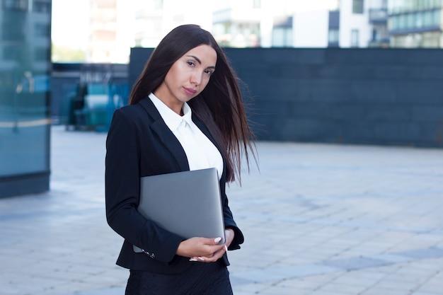 屋外のラップトップでスーツで美しいフォーマルな服装の実業家。オフィス、ビジネスセンターの近くに立って、カメラを見てブルネットの白人女性。ガジェット、ノートブックでセクシーな白人少女。