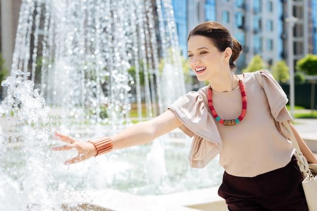 Красивый фонтан. довольно счастливая женщина улыбается, глядя на воду