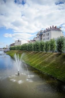 Красивый фонтан на пруду в городе летом