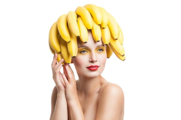 Красивая хрупкая модель с гроздью бананов на голове, глядя в сторону. студия выстрел