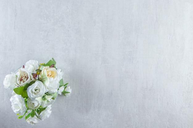 白いテーブルの上に、美しい香りの花とガラス。