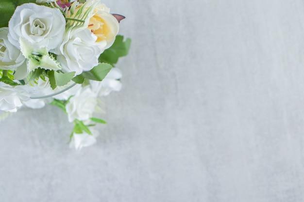 Bei fiori e vetro di fragranza, sulla tavola bianca